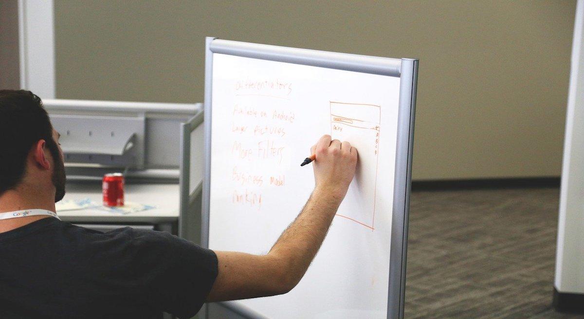 mężczyzna pisze na tablicy